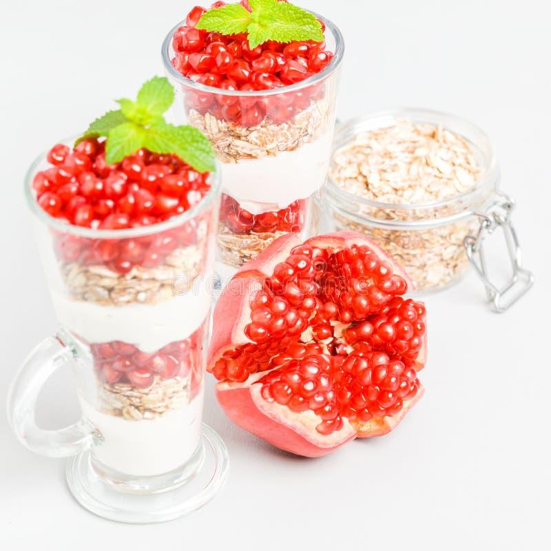 Parfait гранатового дерева - сладостный органический наслоенный десерт с хлопьями granola, югуртом и красными зрелыми семенами пл стоковое изображение rf