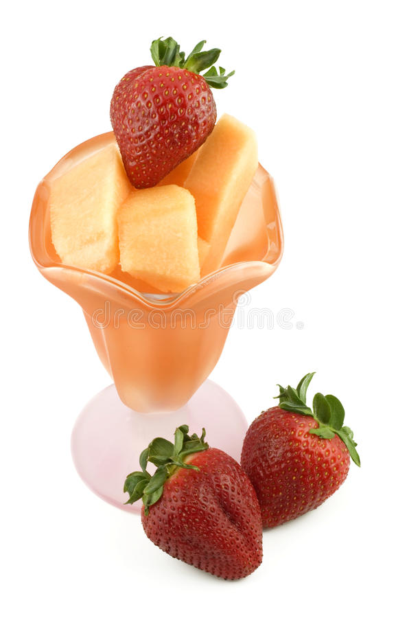 Parfait Dish with Cantaloupe and Strawberries. A orange and pink glass parfait dish filled with cubed cantaloupe and fresh whole strawberries, isolated on white stock images