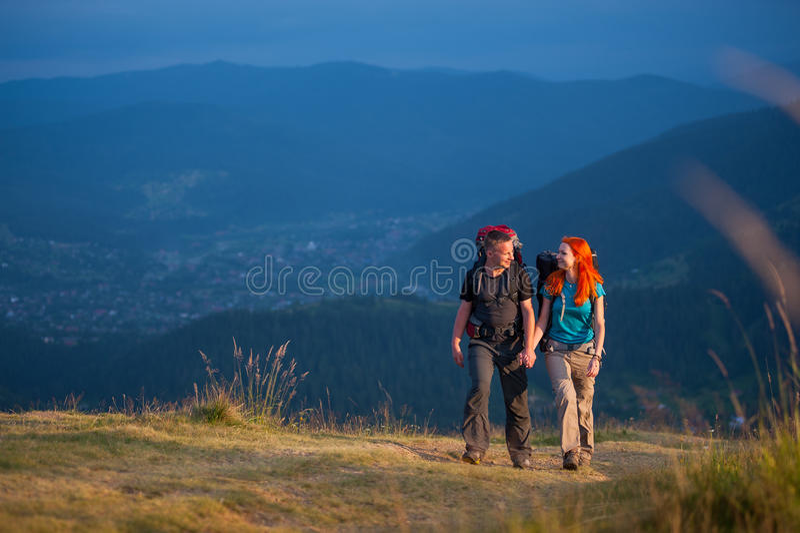 Parfotvandrare med ryggsäckar som rymmer händer som går i bergen royaltyfria bilder