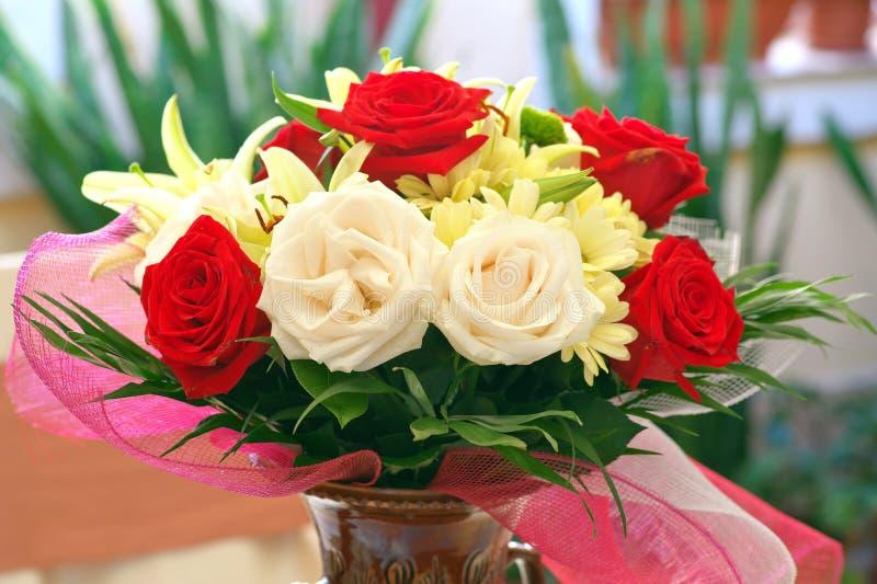Parfum Bloemgeur Bloemenregeling Mooi geparfumeerd boeket met rode rozen, chrysanten en lelies in ceramische vaas stock afbeelding
