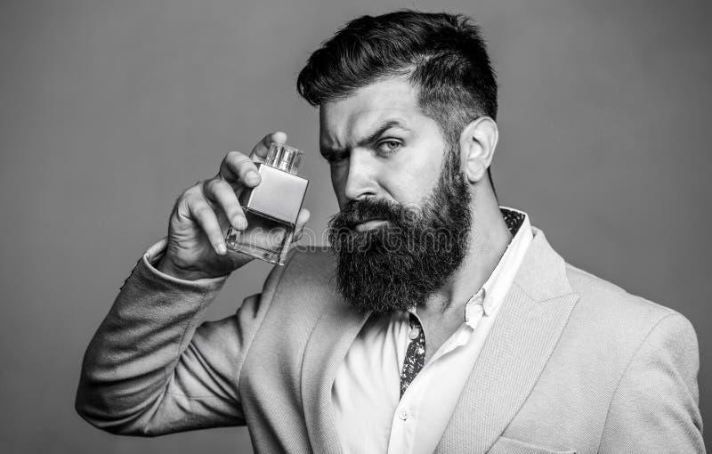Parfum d'homme, parfum Parfum masculin Parfum masculin et parfumerie, cosm?tiques Homme barbu supportant la bouteille de photos stock