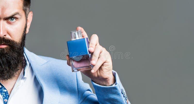 Parfum d'homme, parfum Parfum masculin Parfum masculin et parfumerie, cosm?tiques Homme barbu supportant la bouteille de photo stock