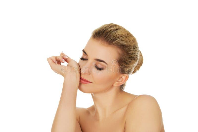 Parfum sentant de jeune femme sur son poignet photographie stock