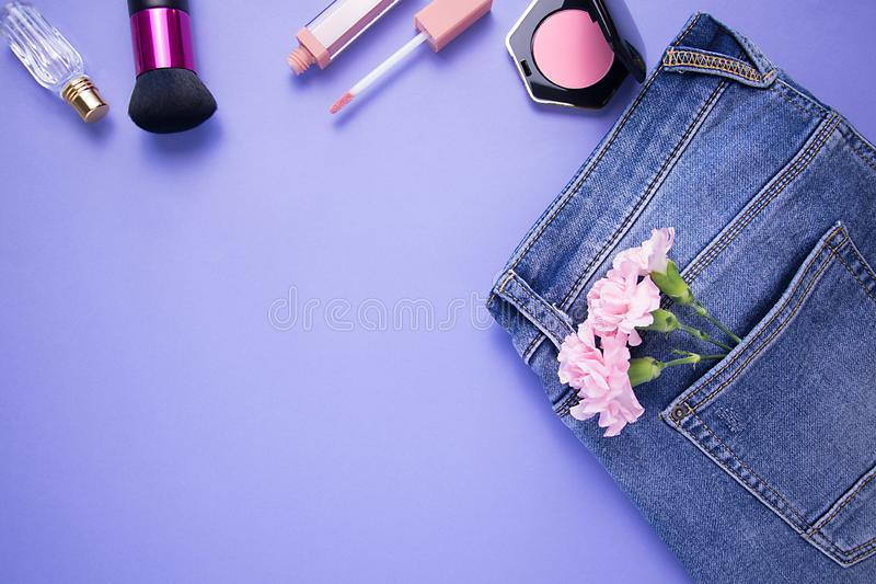 Parfume, brush, lipstick, blush and jeans with pink carnation flowers on purple background. Spring`s consept stock photos