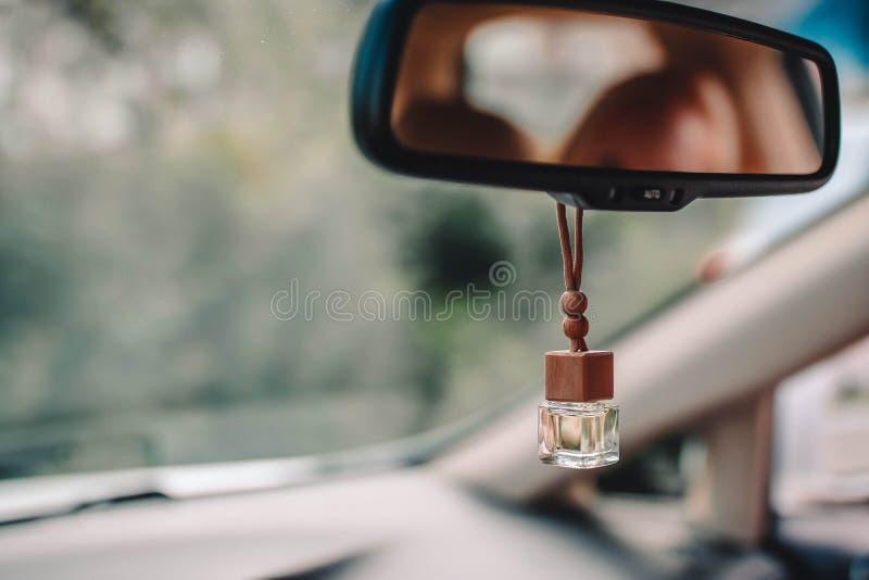 Parfume do ar do carro no espelho frontal do carro com fundo verde borrado fora da janela imagens de stock