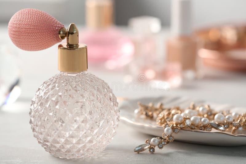 Parfumez la bouteille et les bijoux sur la table photo libre de droits