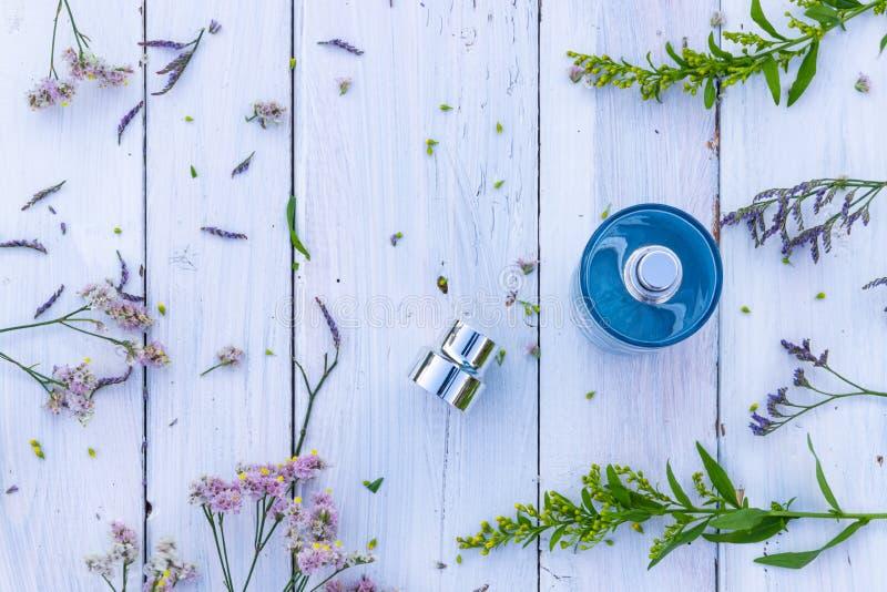 Parfumfles omgeven door verse bloemen op houten achtergrond stock fotografie