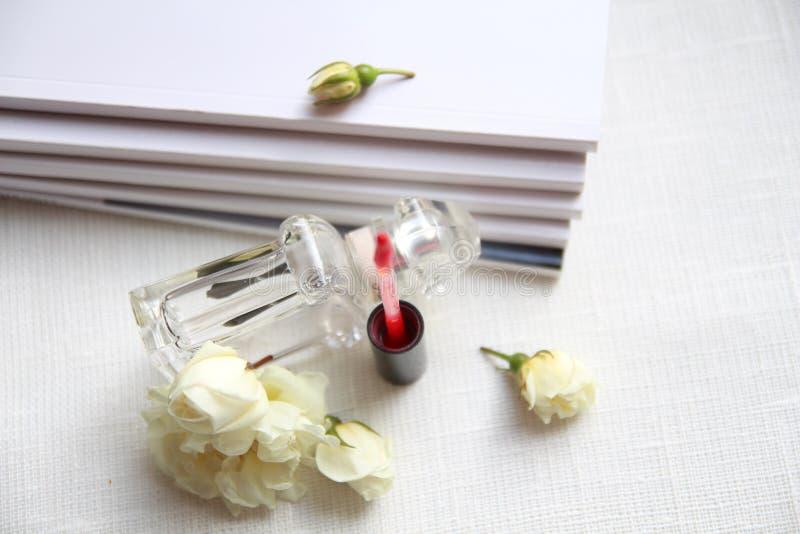 Parfumfles, rode lippenstift, witte rozen en tijdschriften stock foto