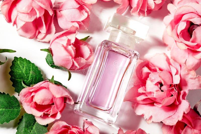 Parfumfles in roze bloemrozen De lenteachtergrond met luxearoma parfume Schoonheids kosmetisch schot stock afbeelding