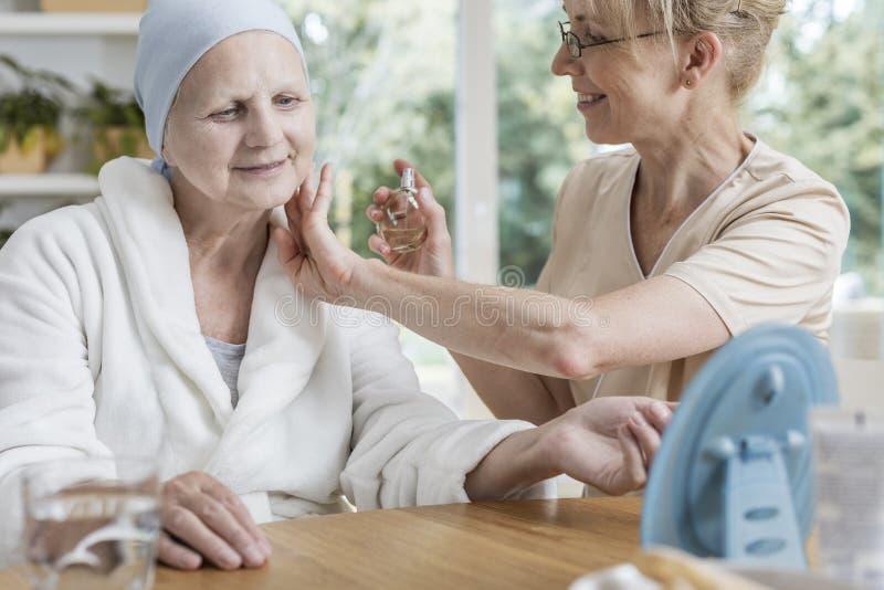 Parfums de pulvérisation de travailleur social heureux sur la femme supérieure malade avec le cancer du sein photographie stock libre de droits