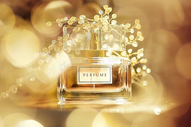 Parfymera flaskan på guld- bokehbakgrund Aromatisk Eau de Toilette royaltyfri foto