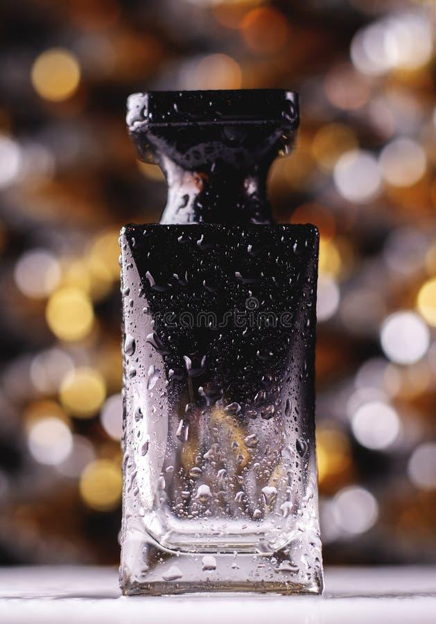 Parfymera flaskan p? guld- bokehbakgrund Aromatisk Eau de Toilette arkivfoto