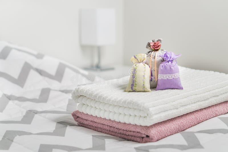 Parfymerade påsar på handdukar på säng Doftande påsar för slags tvåsittssoffahem Torkad lavendel i garneringpåsar i sovrum arkivfoton