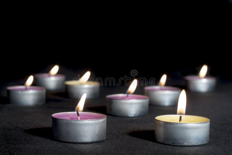 Parfymerade stearinljus av olika dofter, på svart fotografering för bildbyråer