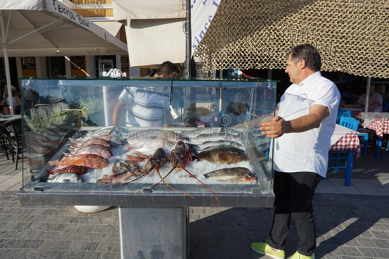 Parga, Greece, 17 July 2018 A restaurateur prepares fresh fish for customers on the seafront royalty free stock photo