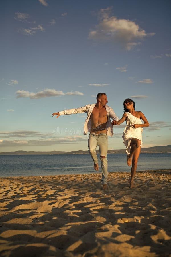 Parhemlighetfantasi Man- och kvinnahållhänder, kopplar ihop lyckligt på semester Förälskad ställning för par på stranden, kust royaltyfria foton