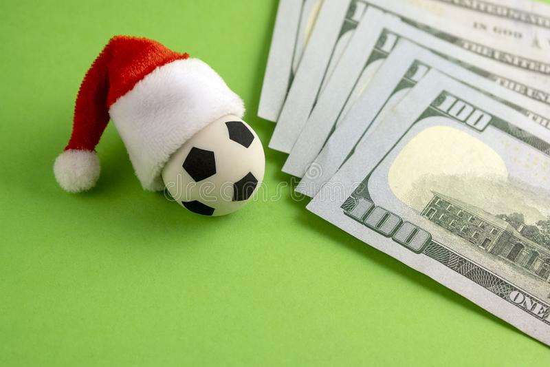 Pari de sports de nouvelle année Ballon de football de souvenir dans un chapeau rouge de Santa Claus à côté des dollars sur un fo image stock