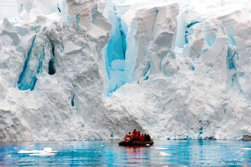 Parida del glaciar en el antártico, gente en zodiaco delante de la escarpa del glaciar imagen de archivo