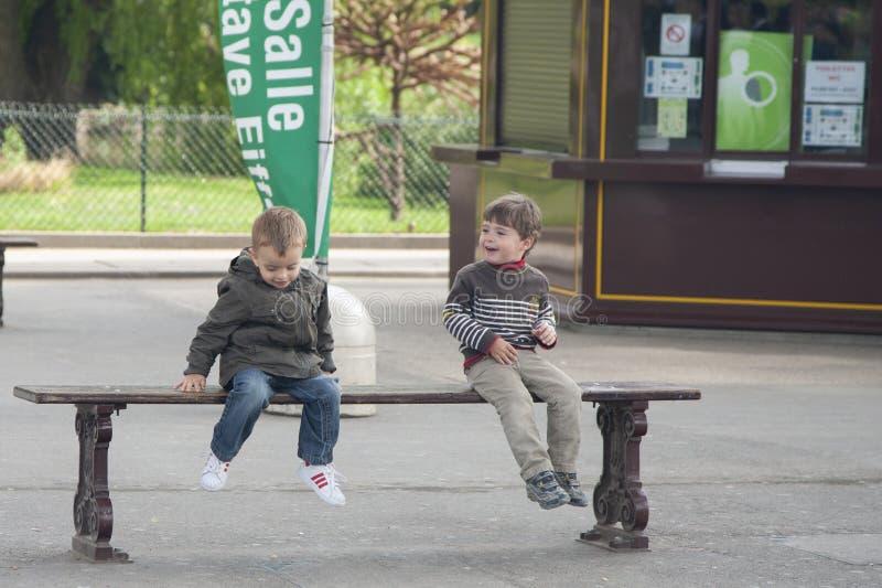 Parijs, Frankrijk - April 12, 2011: De jongens zitten op de bank en het spreken stock fotografie