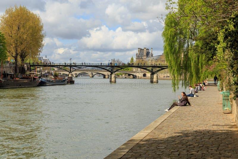 Parijs, Frankrijk, 1 April 2017: De mensen genieten zon van licht door Rivierzegen Met de bevolking van 2M, is Parijs het kapitaa royalty-vrije stock fotografie