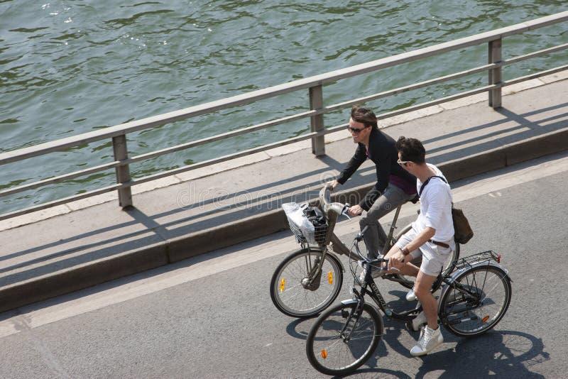 Parijs, Frankrijk - April 17, 2011: Een groep die mensen fietsen langs de rivierdijk berijden stock foto