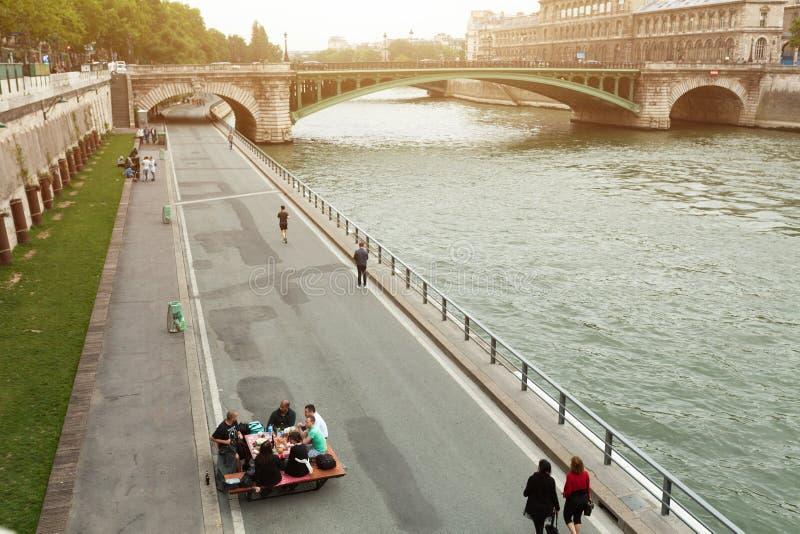Parijs, Frankrijk 01 de metgezel van Juni 2018 A van jongeren drinkt en eet op de banken van de Rivierzegen in het centrum van Pa stock afbeelding