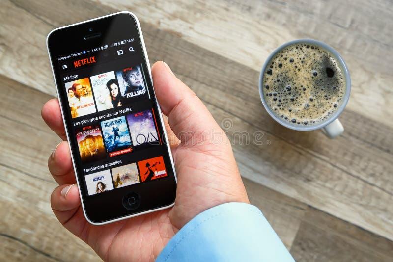 Parijs, Frankrijk - Maart 10, 2017: De mens houdt een slimme telefoon die films van Netflix Frankrijk toont Netflix is een vermaa stock foto's