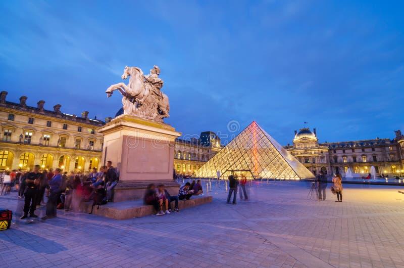 Parijs, Frankrijk - Mei 14, 2015: Toeristen die Louvremuseum bezoeken bij Schemer stock afbeelding