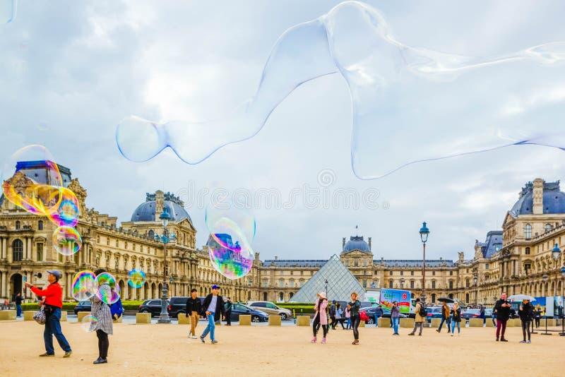 PARIJS, FRANKRIJK - MEI 09, 2019: Weergeven van glaspiramide en Louvremuseum door multi-colored zeepbels van straat het onderhoud stock afbeeldingen