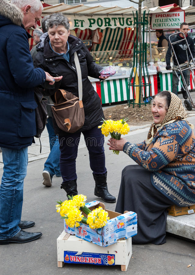 De glimlachende hogere vrouw verkoopt gele narcissuses aan kopers bij markt stock fotografie
