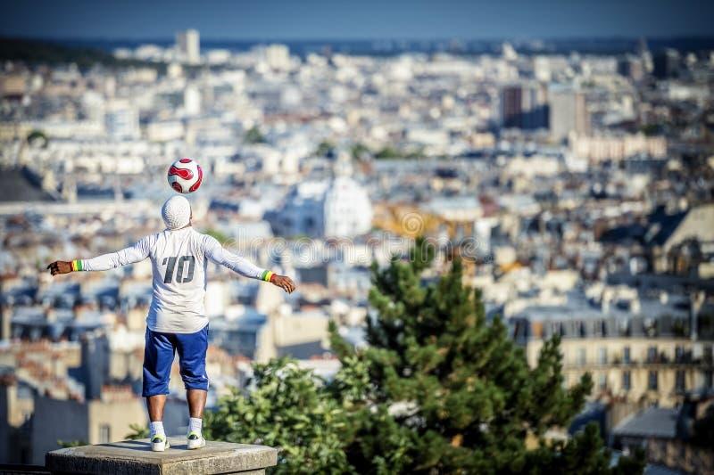 Parijs, Montmatre: Jongensdribbles van hoofd met een grote mening van Parijs op de achtergrond stock afbeelding