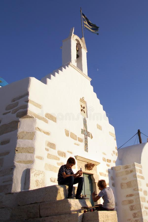 Parikia Grekland, September 16 2018, grekisk barnlek nära kyrkan av Agios Konstantinou, en traditionell Cycladic kyrka arkivfoton