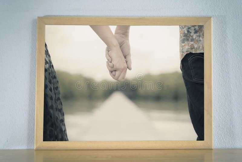 Parinnehavhänder i bildramen som förläggas på den wood tabellen arkivfoto