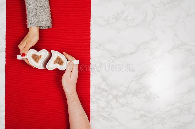 Parinnehavhänder med den vita marmortabellen för kaffe, bästa sikt fotografering för bildbyråer