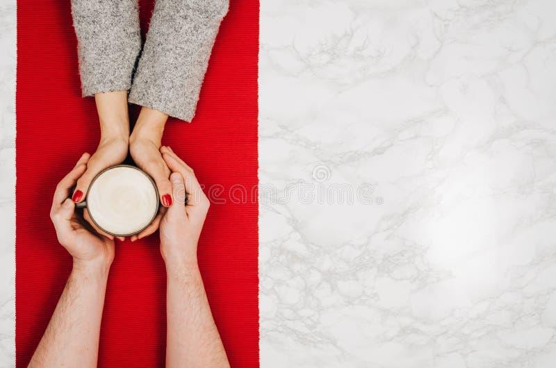 Parinnehavhänder med den vita marmortabellen för kaffe, bästa sikt arkivfoton