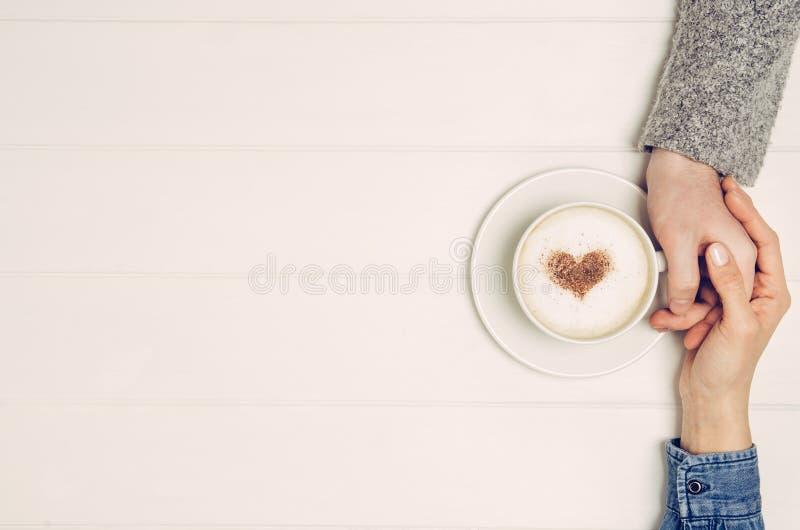 Parinnehavhänder med kaffe på den vita tabellen, bästa sikt fotografering för bildbyråer