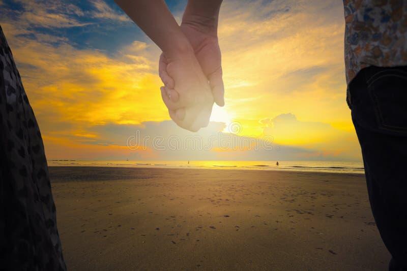 Parinnehavhänder och härlig solnedgång på stranden i backgr arkivfoto