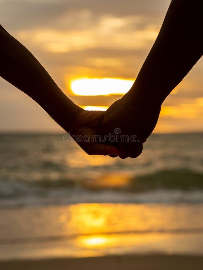 Parinnehavhänder på härlig solnedgångbakgrund på stranden royaltyfri fotografi