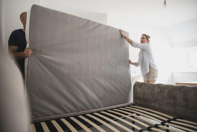 Parinställning - upp säng tillsammans i nytt hem royaltyfri fotografi