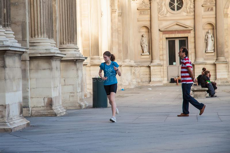 Young girl running along the walls of the Louvre Museum royalty free stock photo