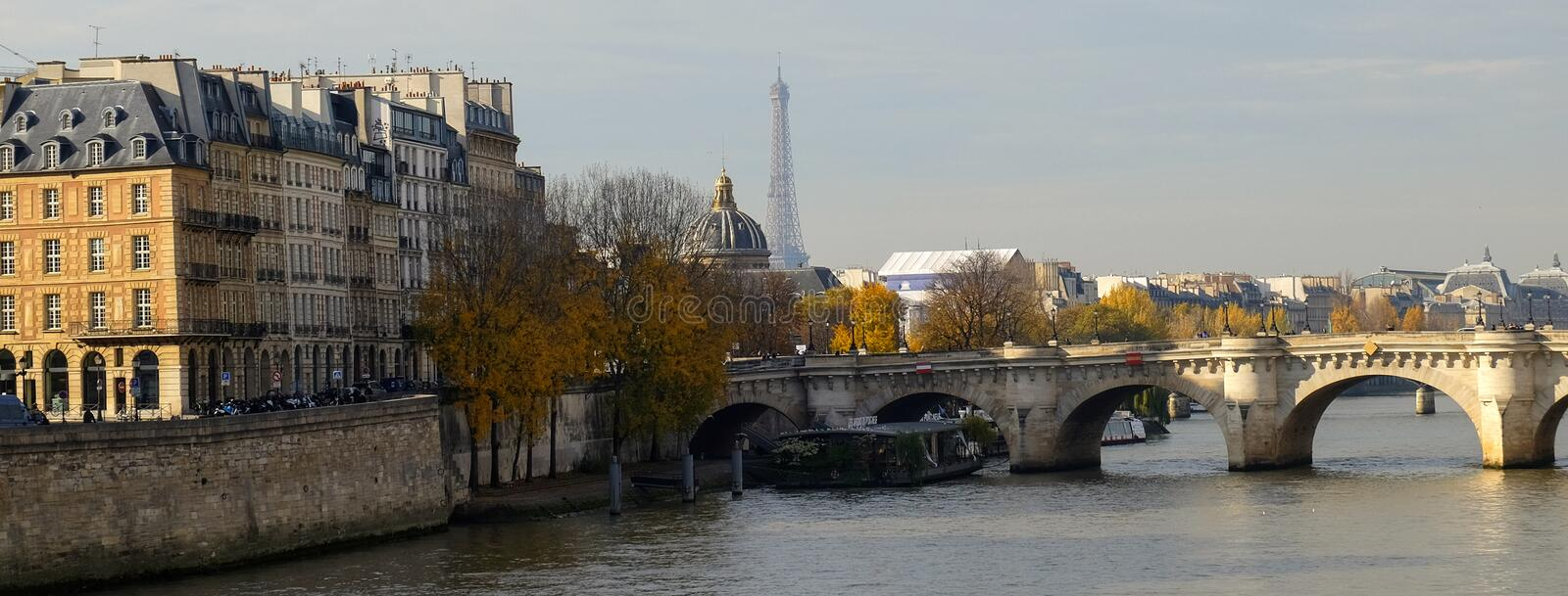 Paris in Autumn. The sun lights the river Seine, the turned yellow trees ashore and beautiful houses which make an architectural c royalty free stock images