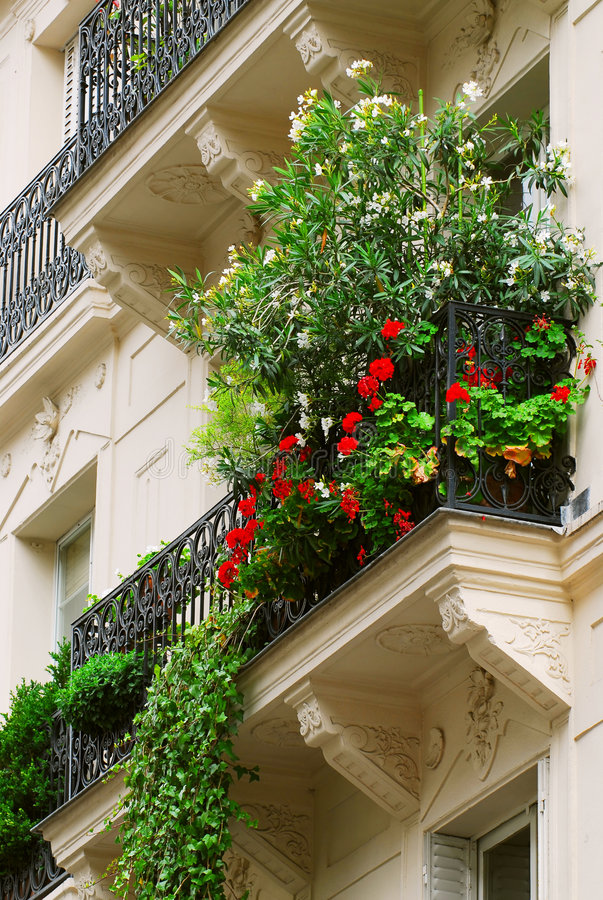 Paris balcony. Wrought iron balcony full of flowers on historic building in Paris, France stock image