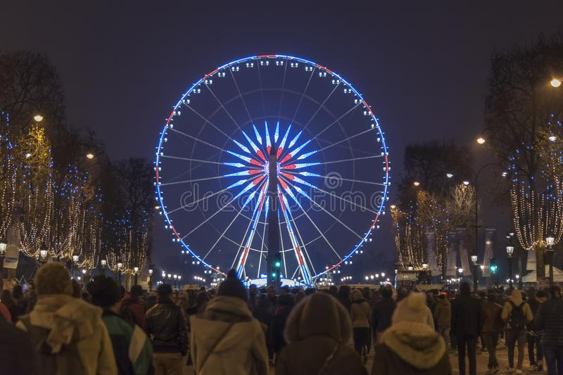 Paris Champs Elysee Ferris wheel. New year celebration crowd walking up from the Champs Elysées to Concorde place and the Ferris wheel at night, Paris, France