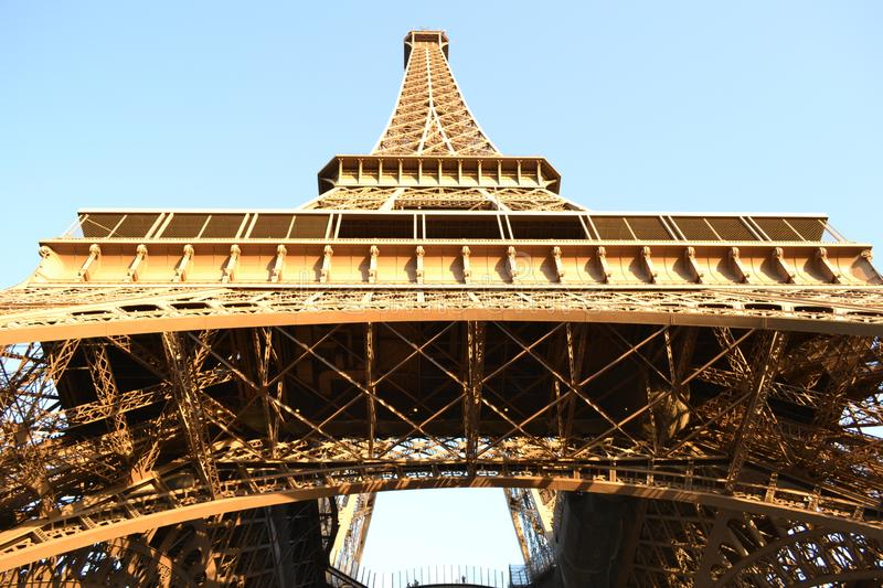 Paris Eiffel Tower complex structure. View to the Paris Eiffel Tower complex structure from the ground on bright blue sky without clouds stock images