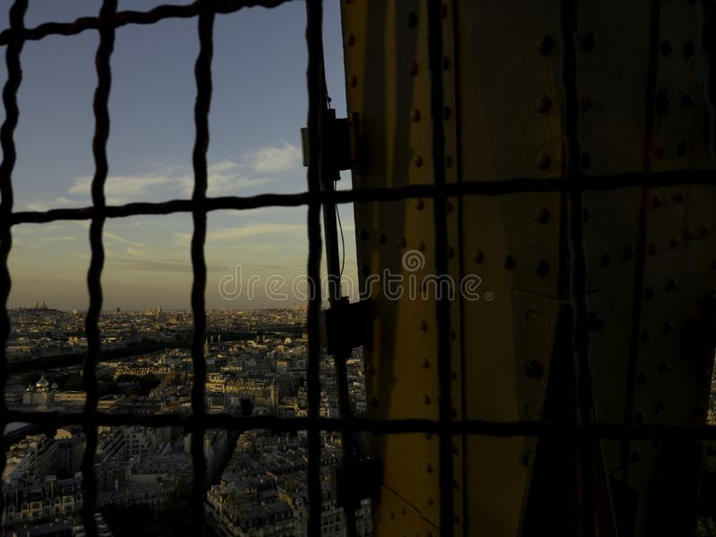 Paris from the Eiffel Tower. A shot of Paris at dusk through metal grating at the Eiffel Tower stock photos