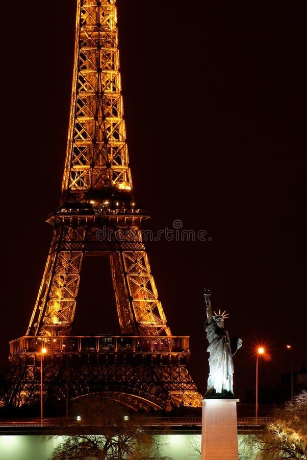 Paris em a noite: Torre Eiffel e estátua de liberdade fotos de stock