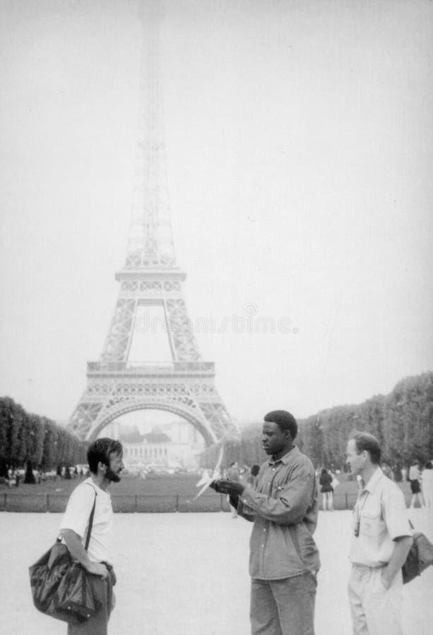 Paris, foto preto e branco velha, em agosto de 1994 Um vendedor ambulante preto está tentando vender um avião do brinquedo imagens de stock