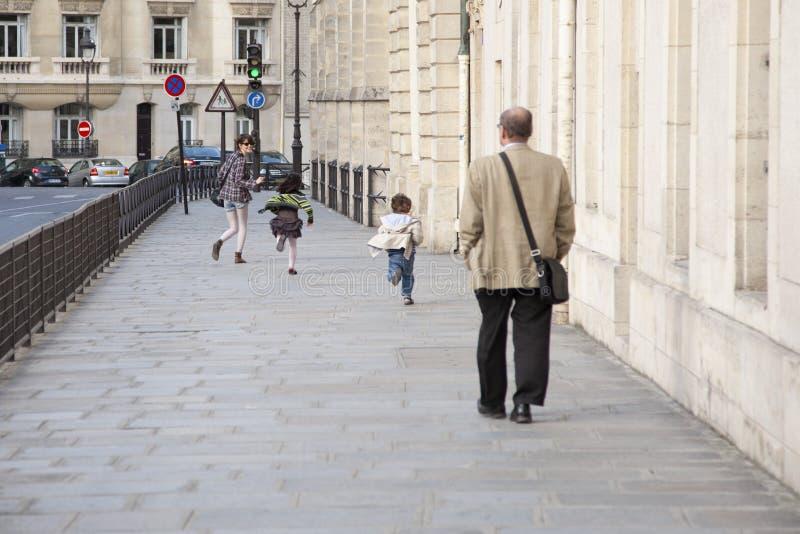 Paris, França - 12 de abril de 2011: Corredor da jovem mulher com as crianças na rua foto de stock royalty free