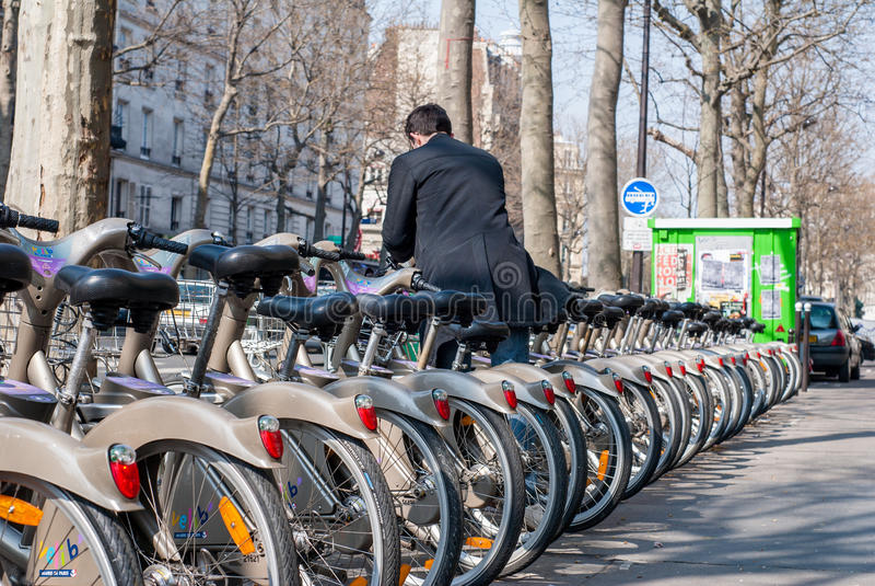 Paris, França - 2 de abril de 2009: Homem novo que deposita sua bicicleta em imagens de stock