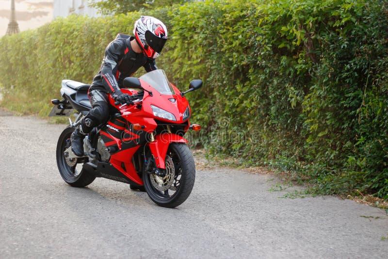 PARIS, FRANÇA - 23 de agosto de 2018: Motociclista bonito na engrenagem completa e capacete em Honda vermelho e preto 2005 CBR 60 fotografia de stock royalty free